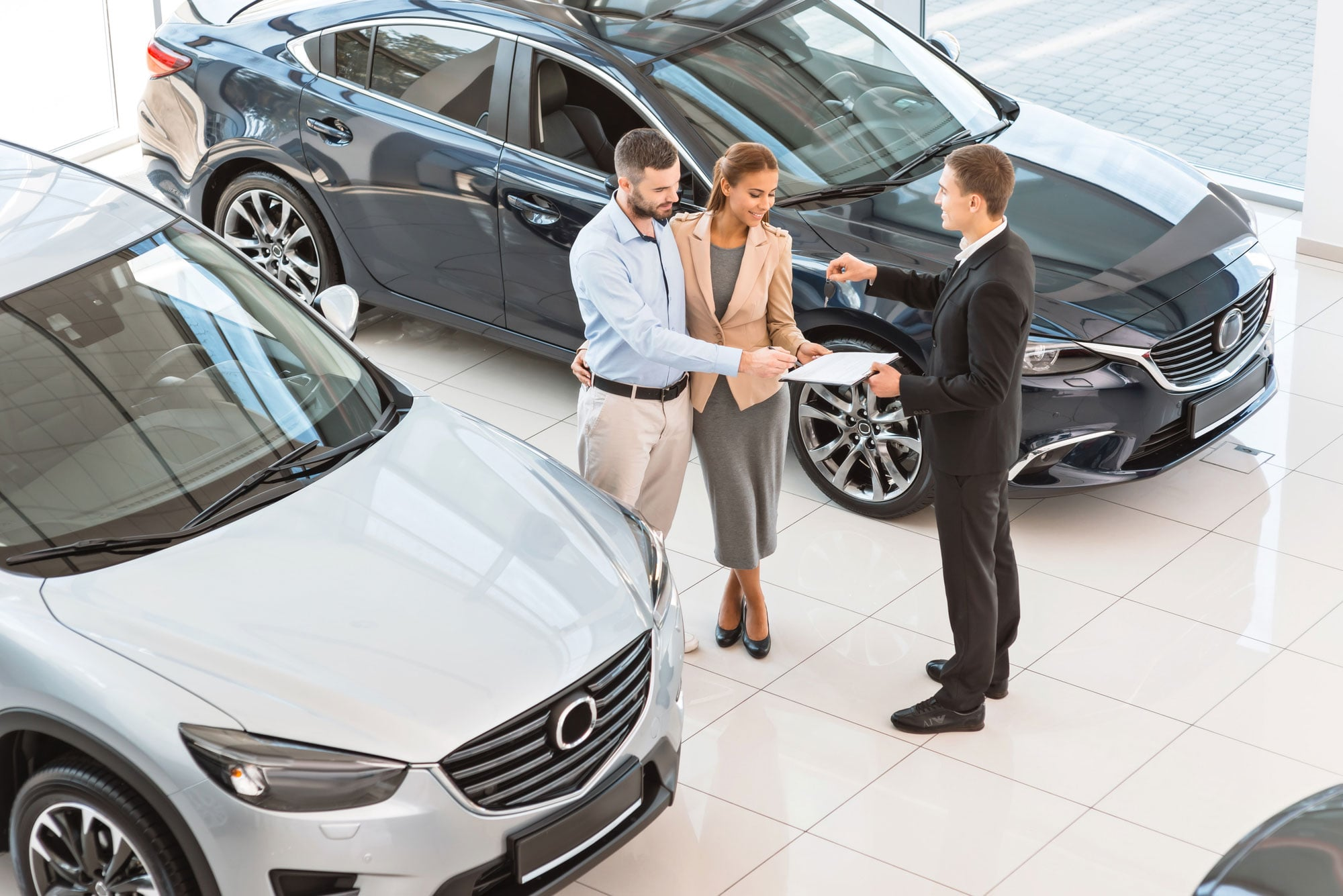 Couple talking with cars salesman